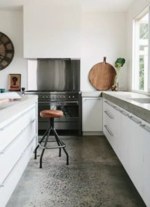 Polished Concrete Kitchen flooring with white cabinetry and wooden stools