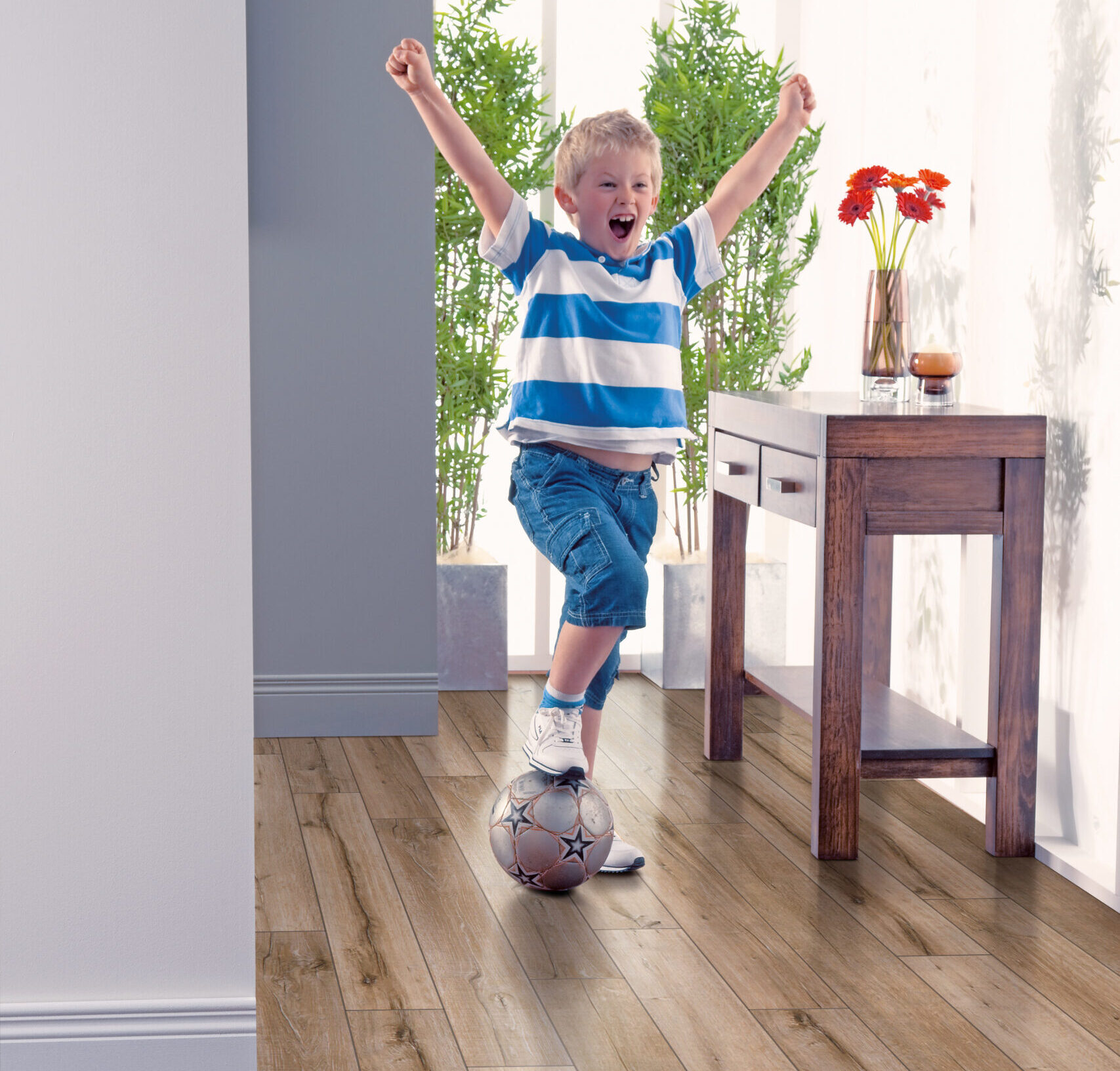 Young boy playing soccer on Elka Salvaged Oak floors